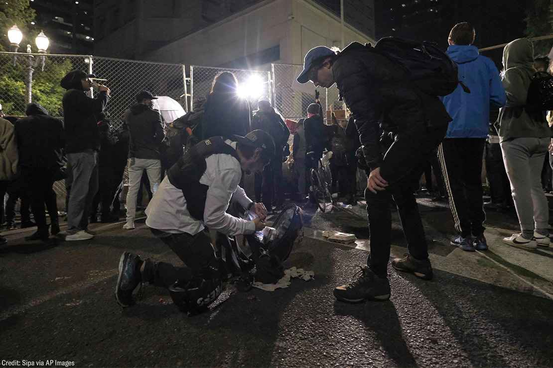 Two journalists prepare for police use of force.