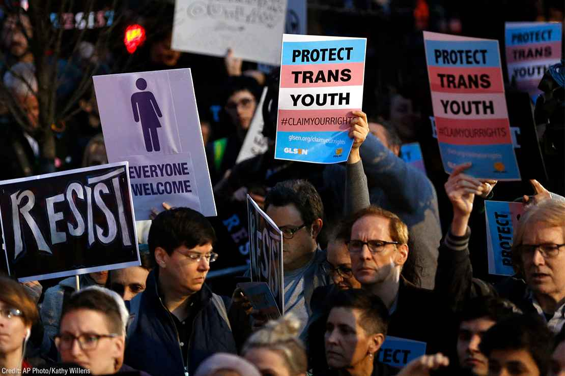Protesters hold signs at a rally in support of transgender youth
