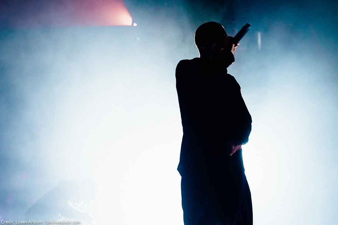 Silhouette of a rapper onstage with bright stage light and smoke in the background.