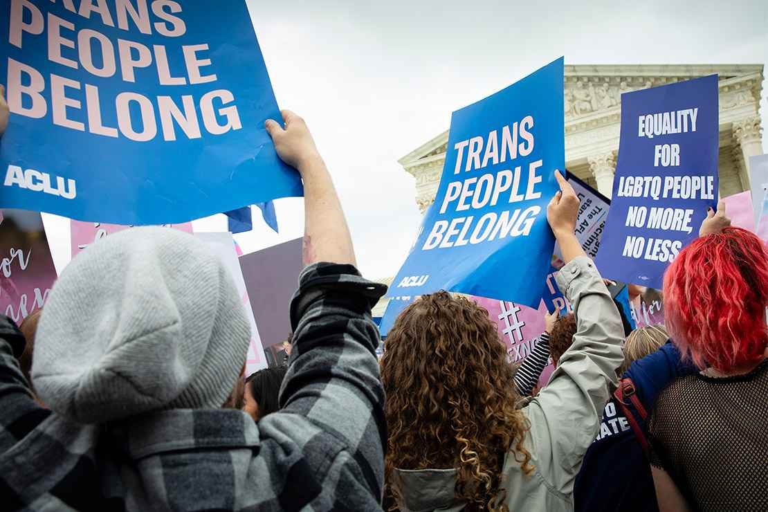 Demonstrators outside the Supreme Court with signs advocating for the rights of LGBTQ people.