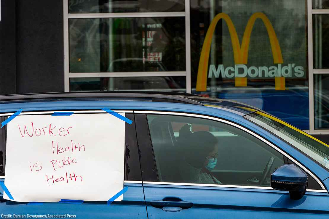 """A protester in a car with a sign reading """"Worker Health is Public Health"""" at a socially distanced protest."""
