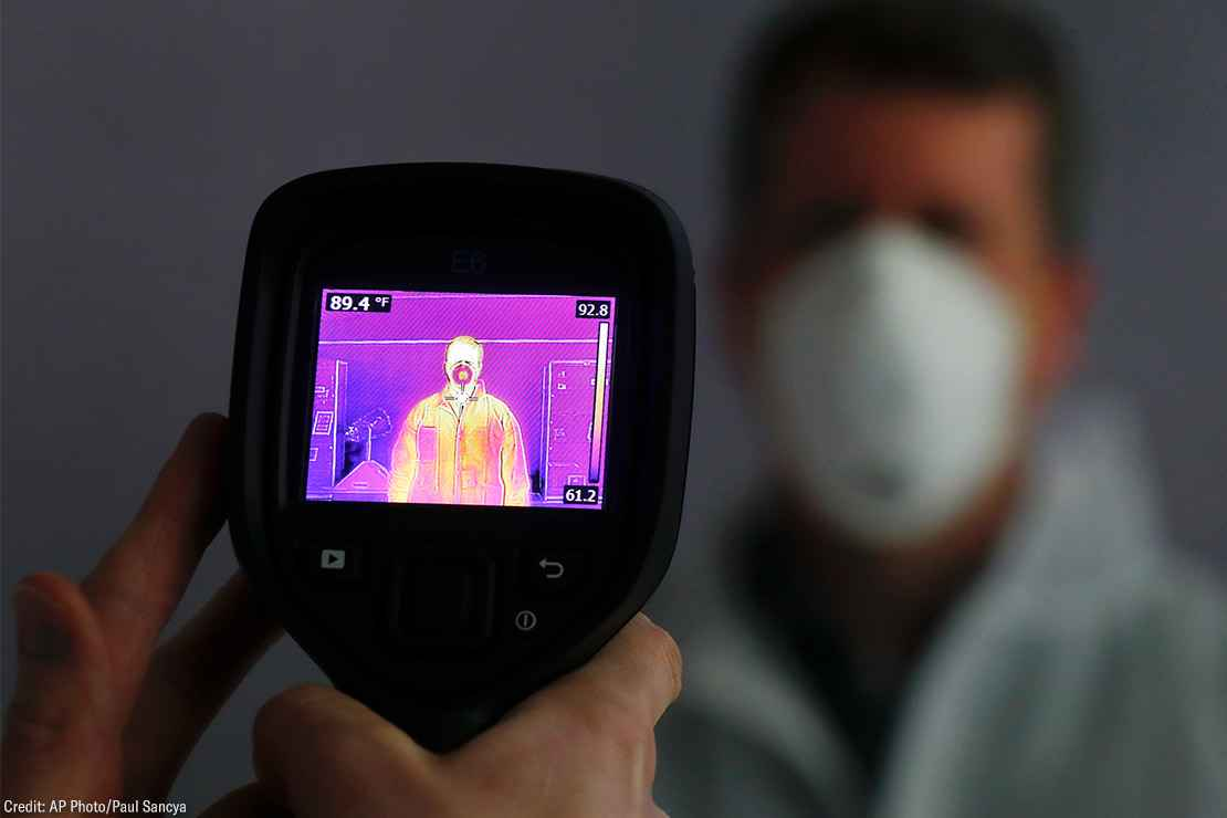 An infrared camera is shown scanning a person for elevated body temperature.