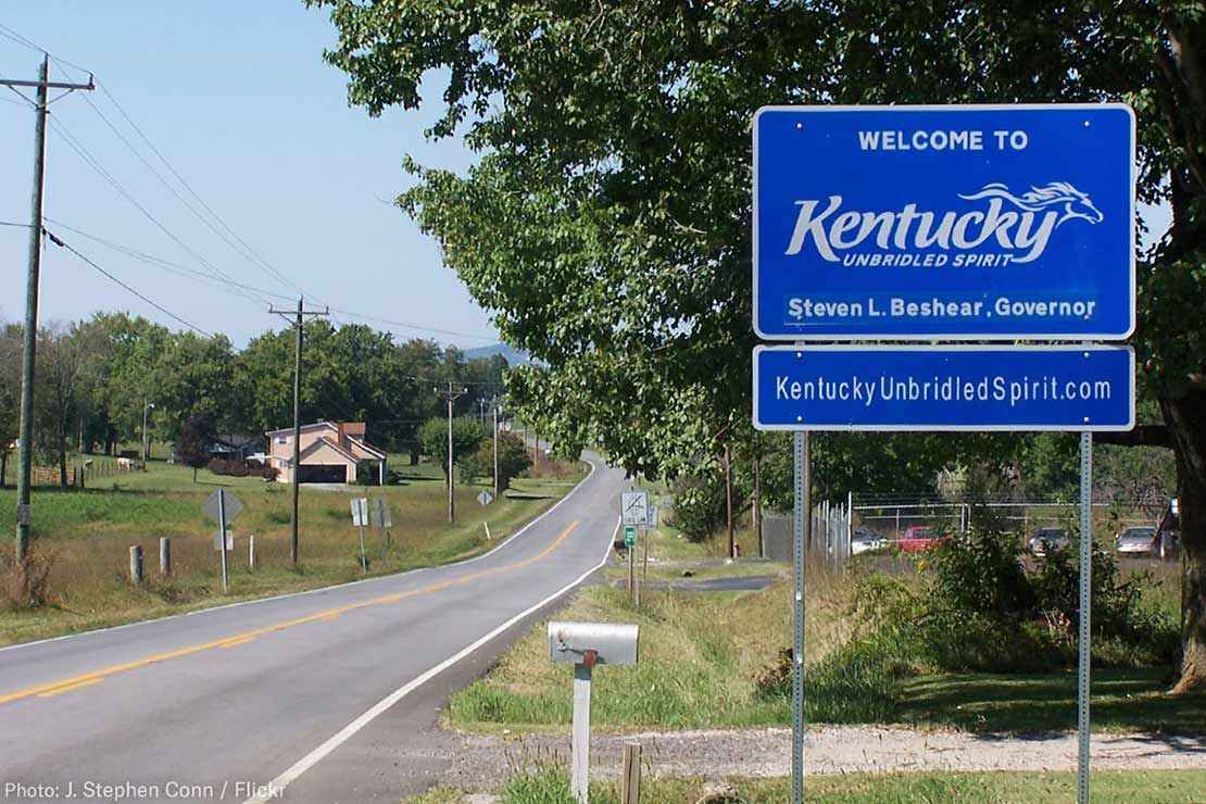 A Welcome to Kentucky road sign with the name of Governor Steven L. Beshear