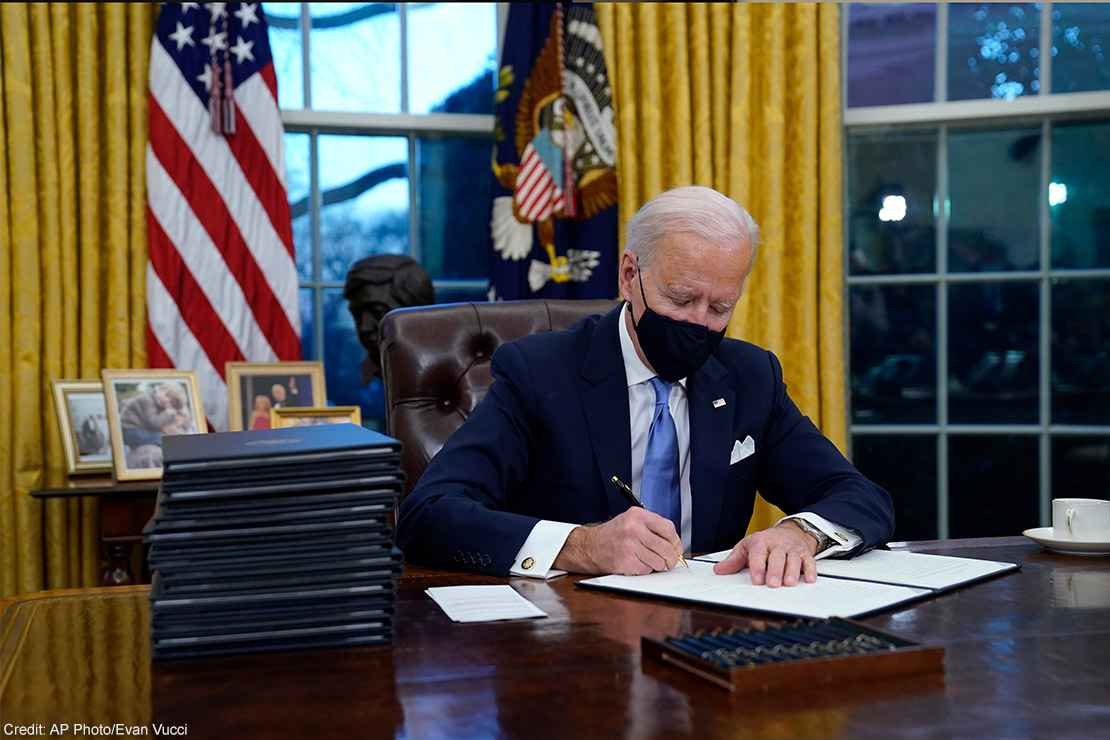 President Joe Biden signs his first executive order in the Oval Office of the White House.