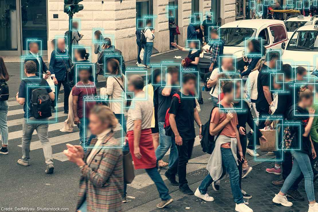 Facial recognition software scanning people walking across a busy intersection.