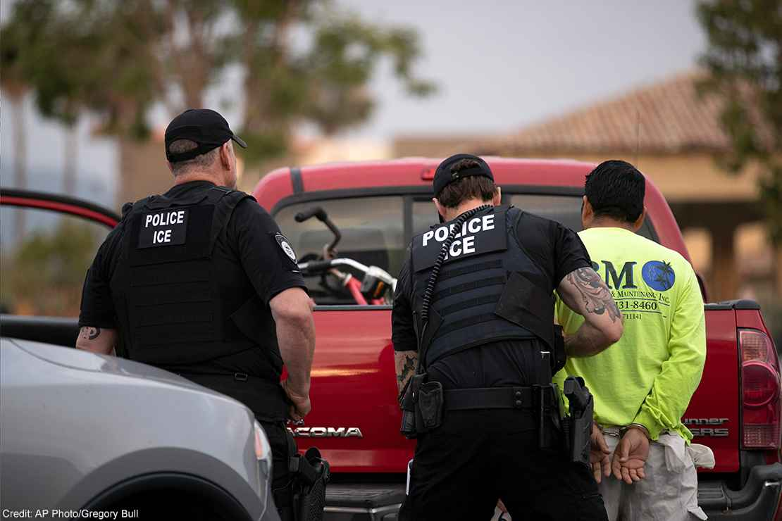 U.S. Immigration and Customs Enforcement (ICE) officers detain someone in front of a red truck.