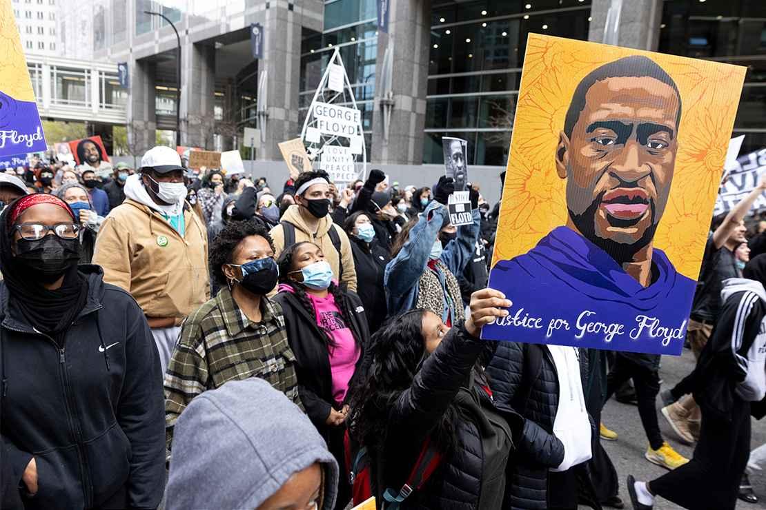 Demonstrators carry signs demanding justice for George Floyd.