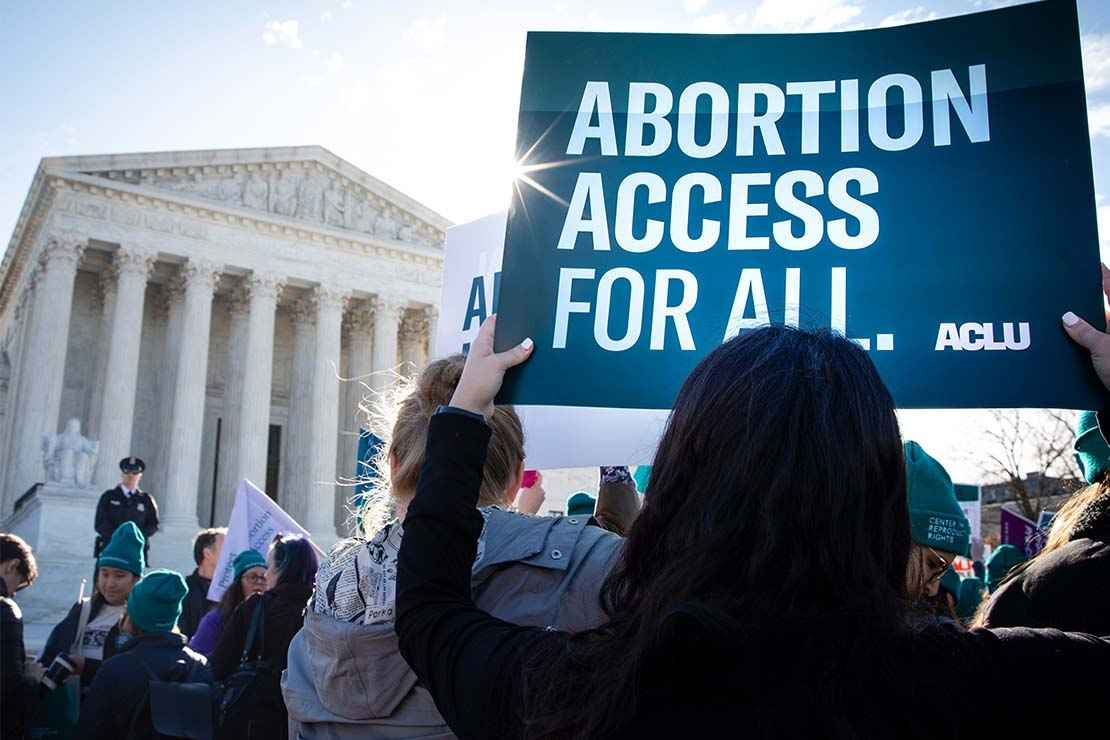 """A protestor holds aloft a sign that says """"Abortion Access for All"""" in front of the Supreme Court building in Washington, DC"""