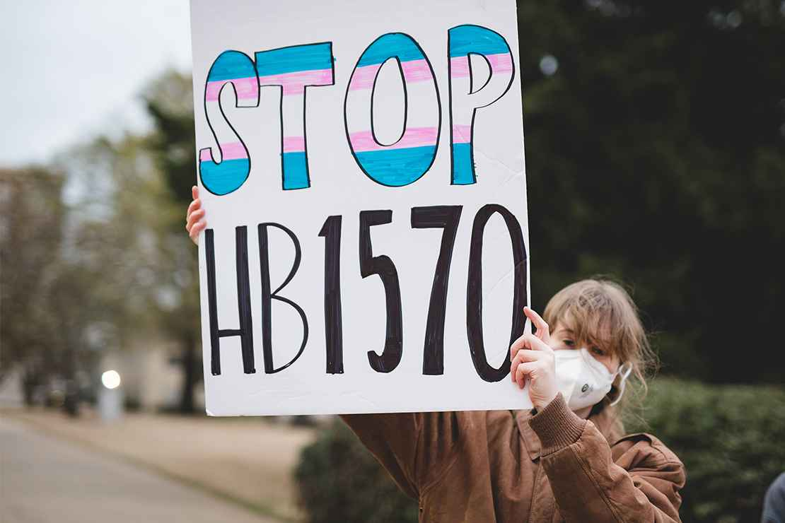 "A demonstrator holding a sign with the text ""Stop HB1570."""