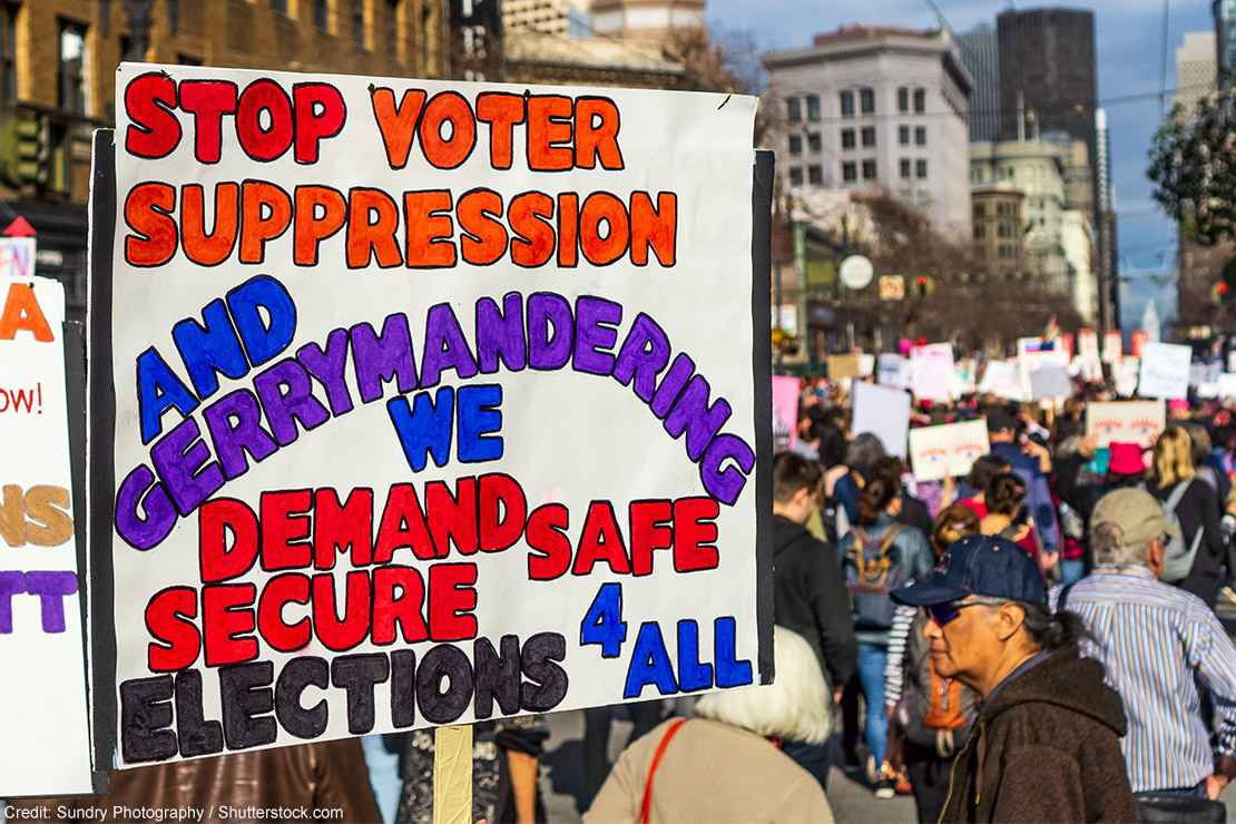 A demonstrator carries a sign demanding an end to gerrymandering and voter suppression.
