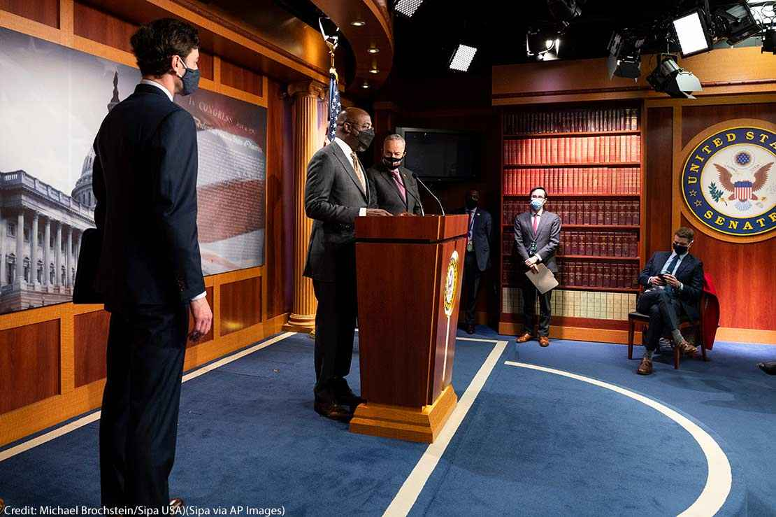 U.S. Senator Raphael Warnock (D-GA) speaking, with U.S. Senator Jon Ossoff (D-GA) and Senate Majority Leader Chuck Schumer (D-NY) standing next to him, about the COVID-19 relief legislation being worked on in the Senate, on February 11. 2021.
