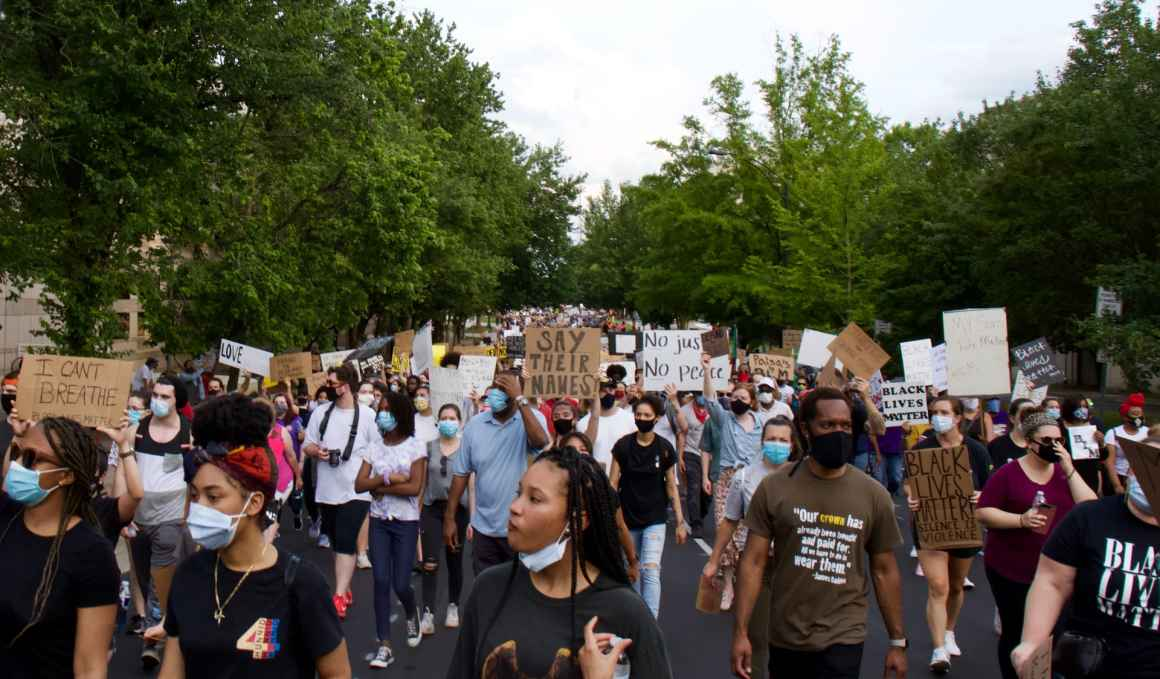 A group of paceful protesters marching in the streets for racial justice.