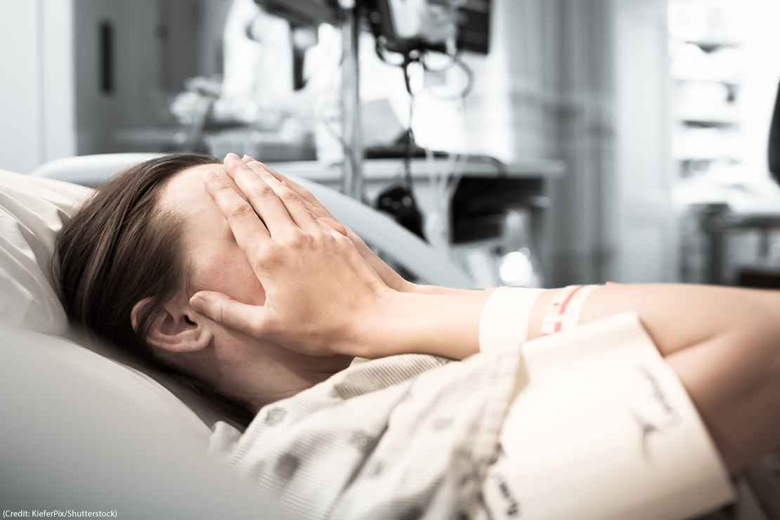 Image of a woman in a hospital bed covering her eyes