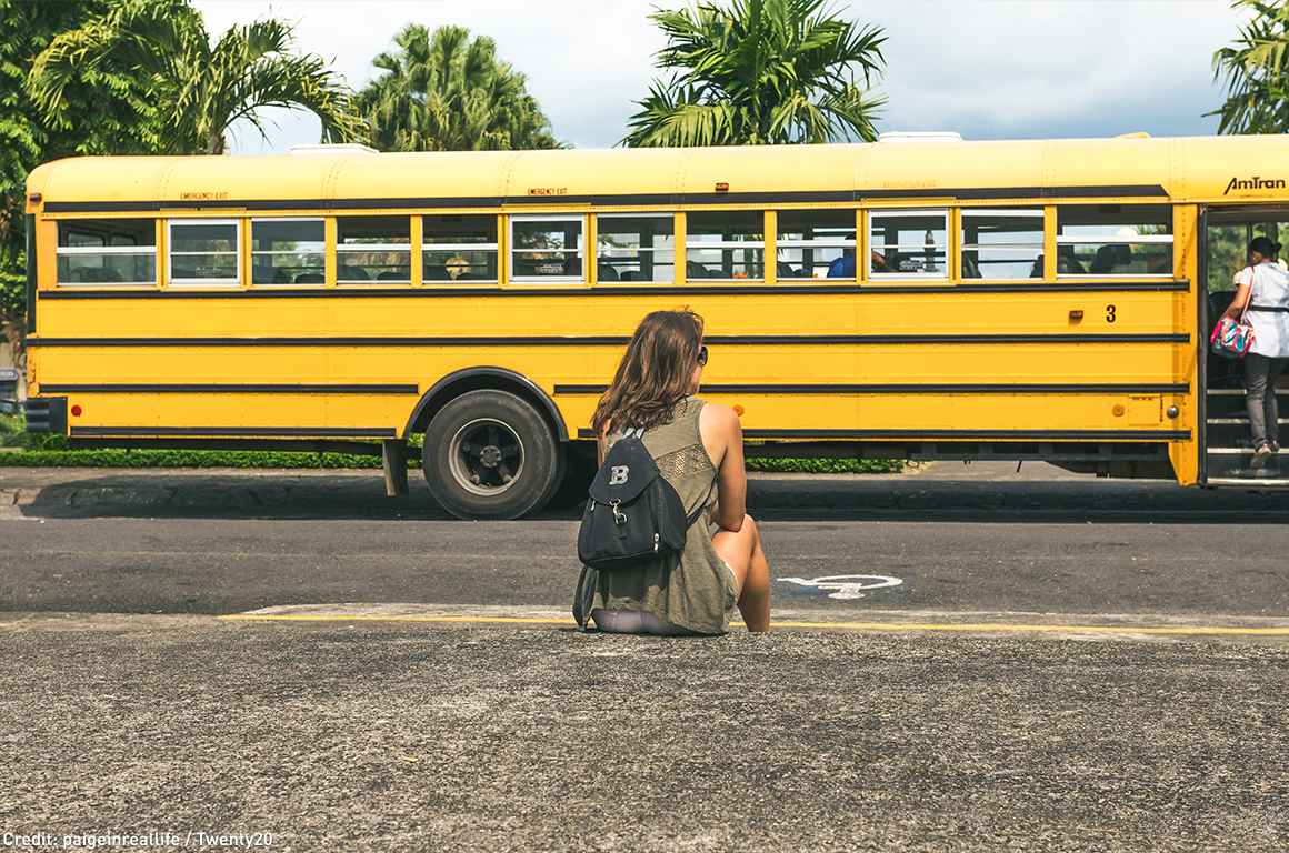 Girl sitting outside with school bus