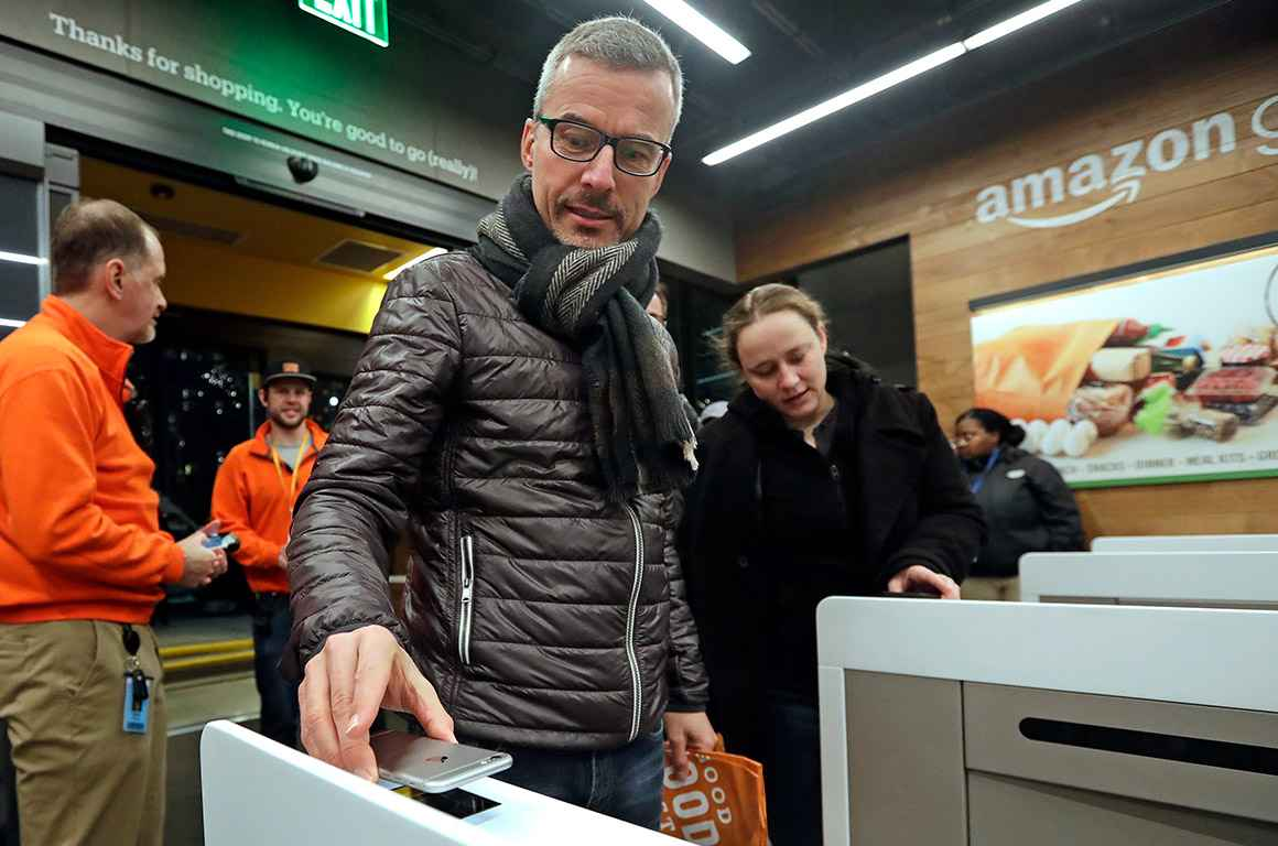 A customer scanning the Amazon Go cellphone app at the entrance of an Amazon Go store