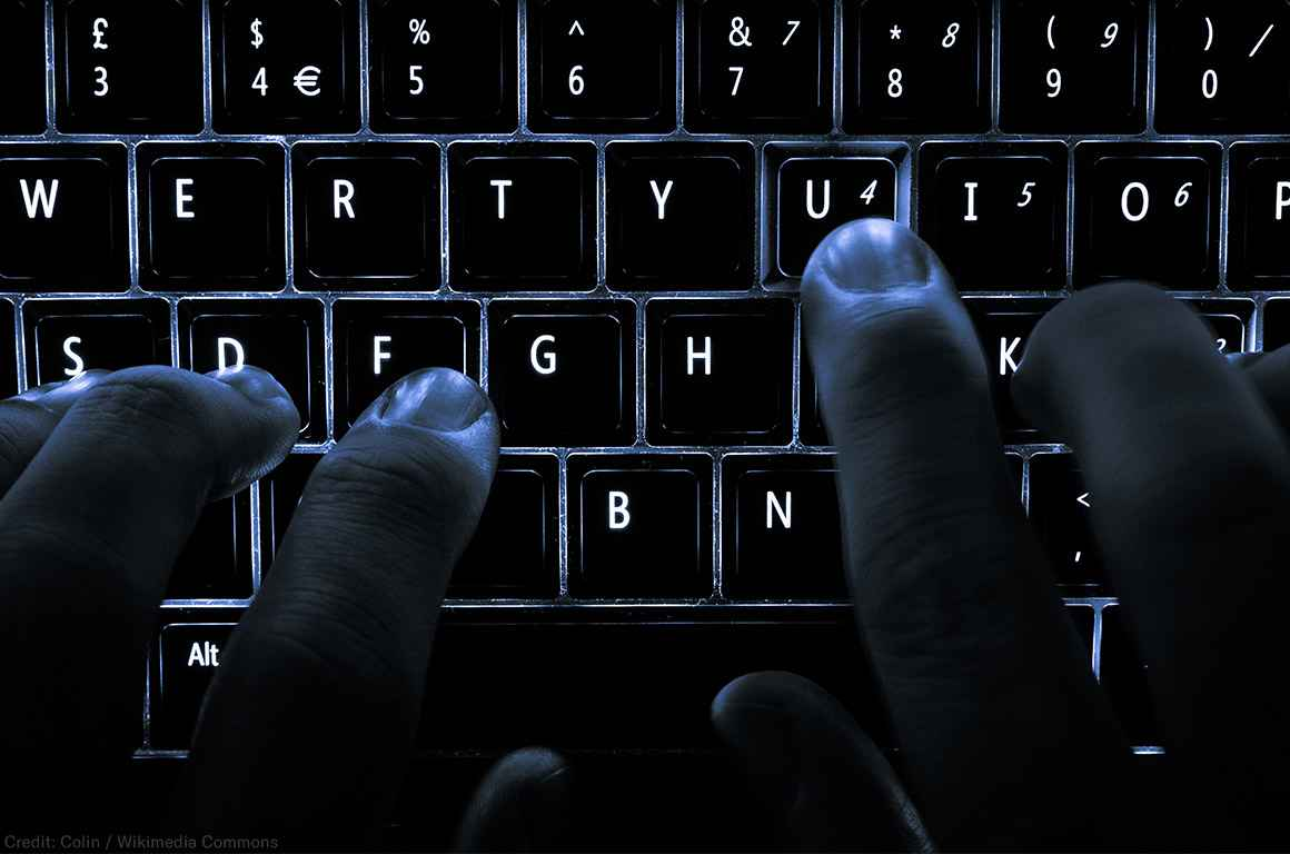 """A backlit laptop computer keyboard. Most fingers are on the """"home"""" keys for touch-typing; the 'U' key is being pressed."""