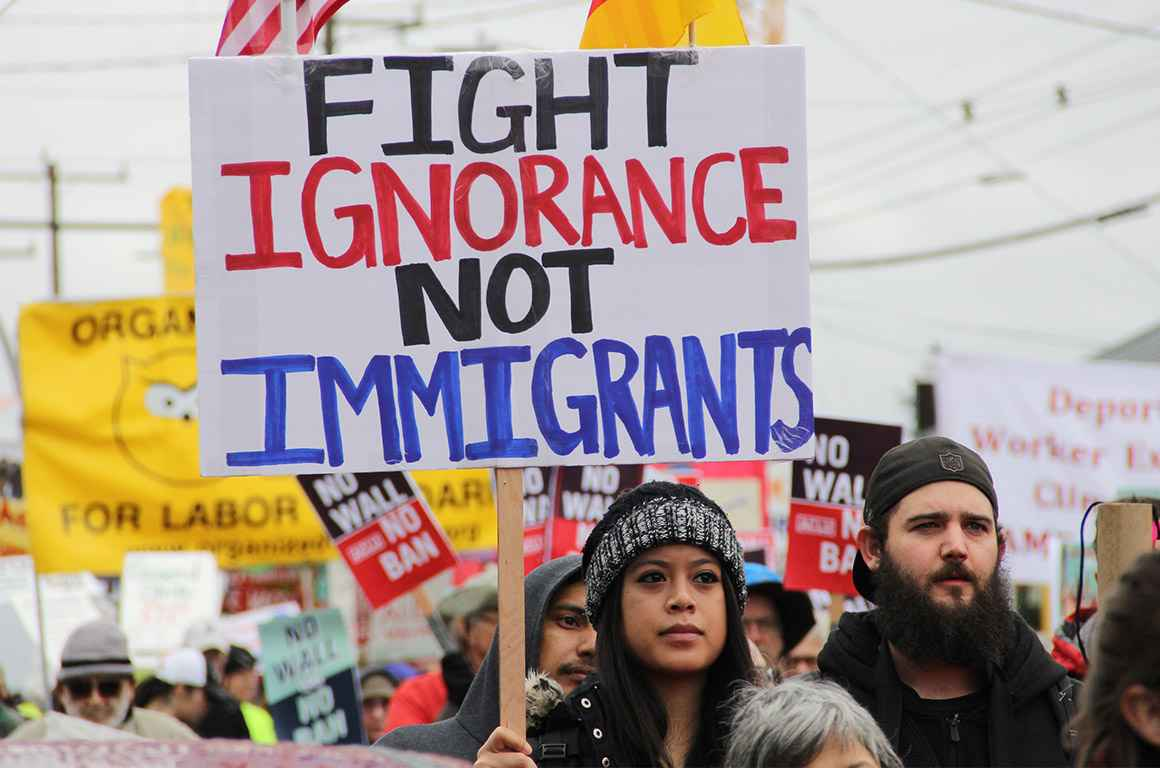 "A protester holding a sign with the text ""fight ignorance not immigrants"""