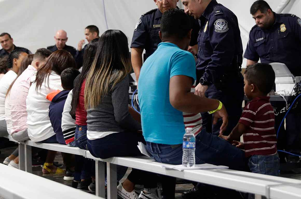 Migrants seated in a processing area at a tent courtroom
