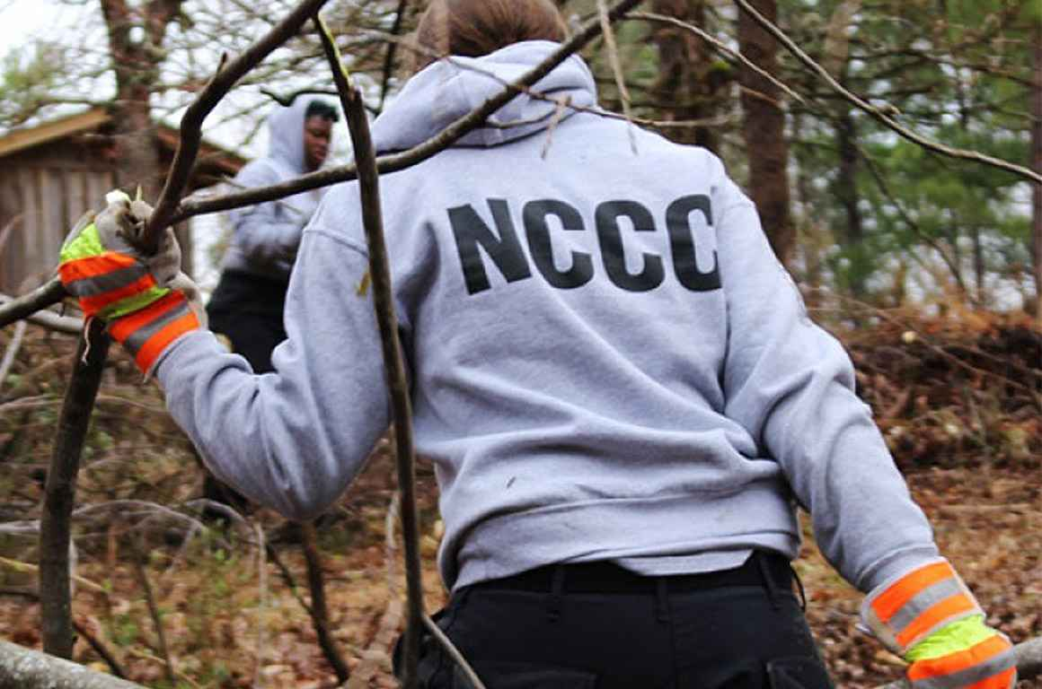 A NCCC worker hauling branches