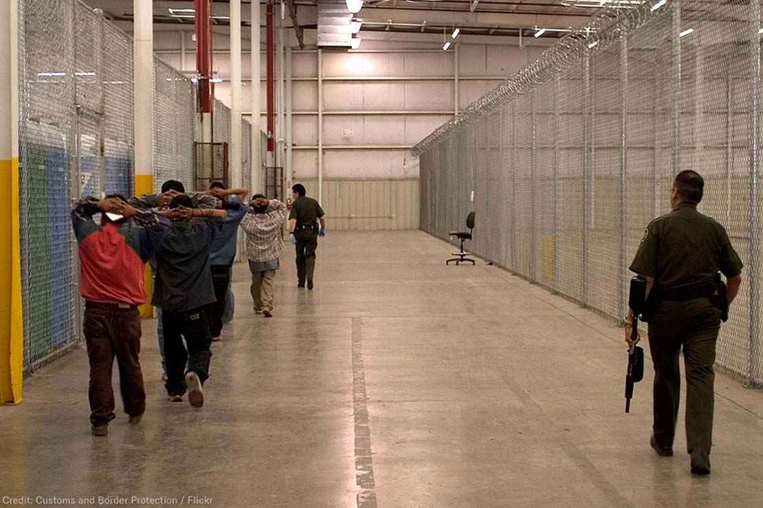 Armed CBP guard watches inmates in a CBP facility