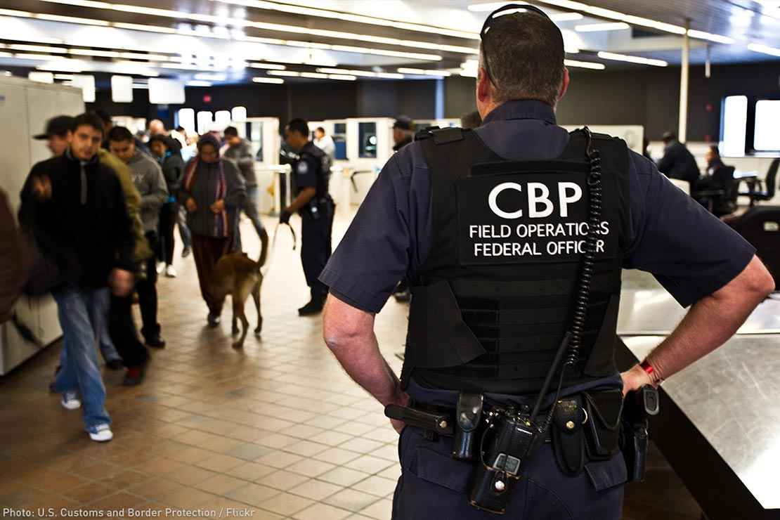 A CBP officer watches over travellers at an airport.