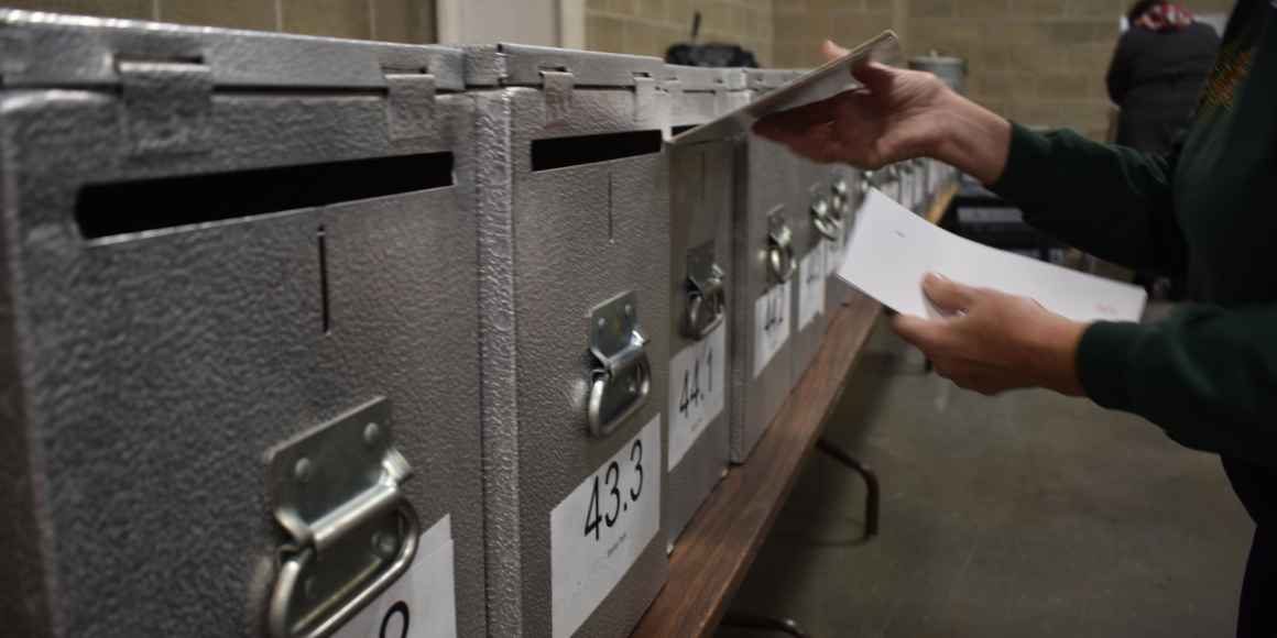 An election worker inserting a ballot into a locked ballot box.