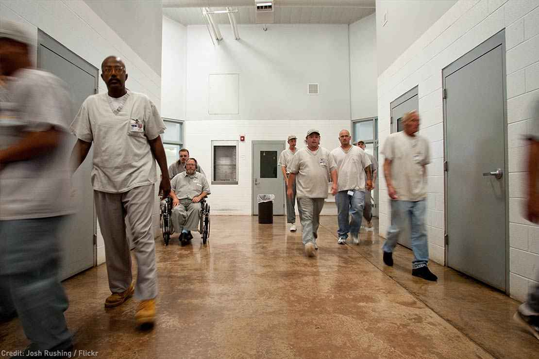 Prisoners are seen walking in a hallway in a prison, one in a wheelchair