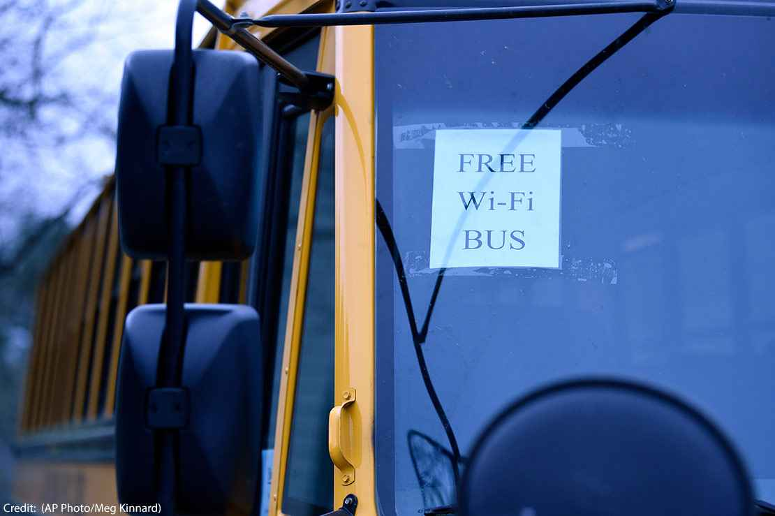 "A sign on a school bus displays ""FREE WIFI BUS"""